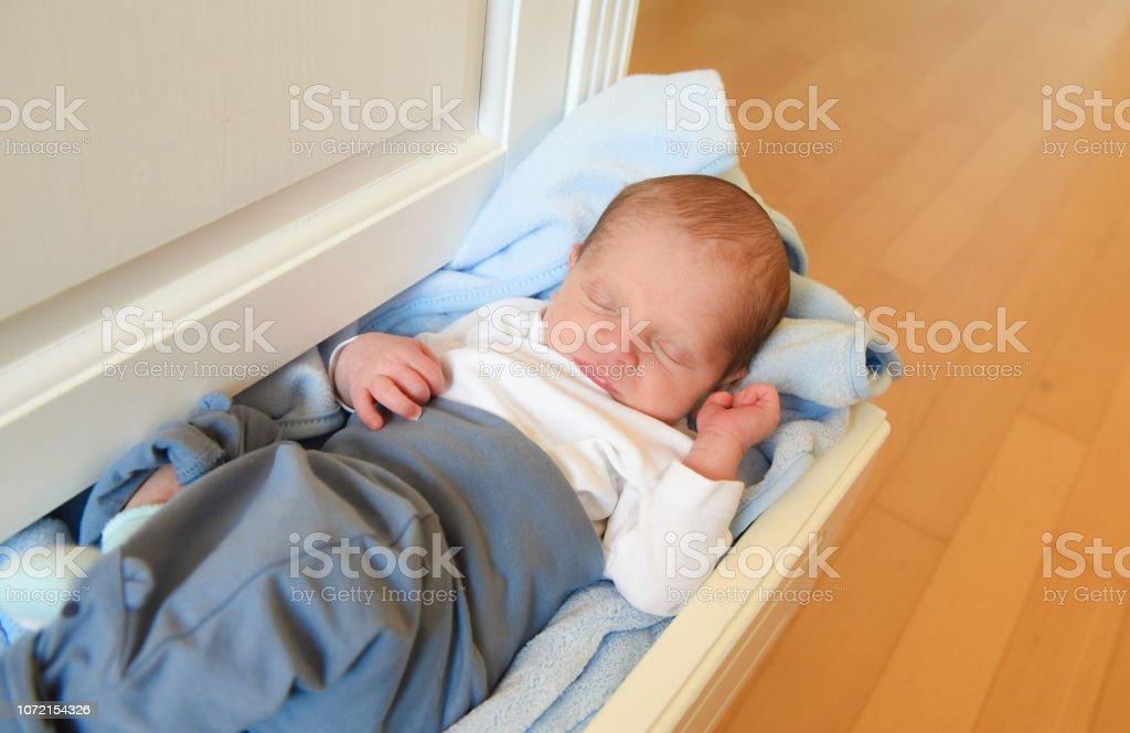 Newborn baby sleeping in a furniture drawer