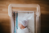 A baby just born at the hospital rests in a hospital bassinet crib, wrapped in a swaddle and wearing a beanie hat.