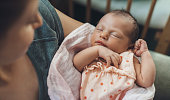 istock Newborn baby sleeping in safety while mother is holding and smiling at her 1286467407