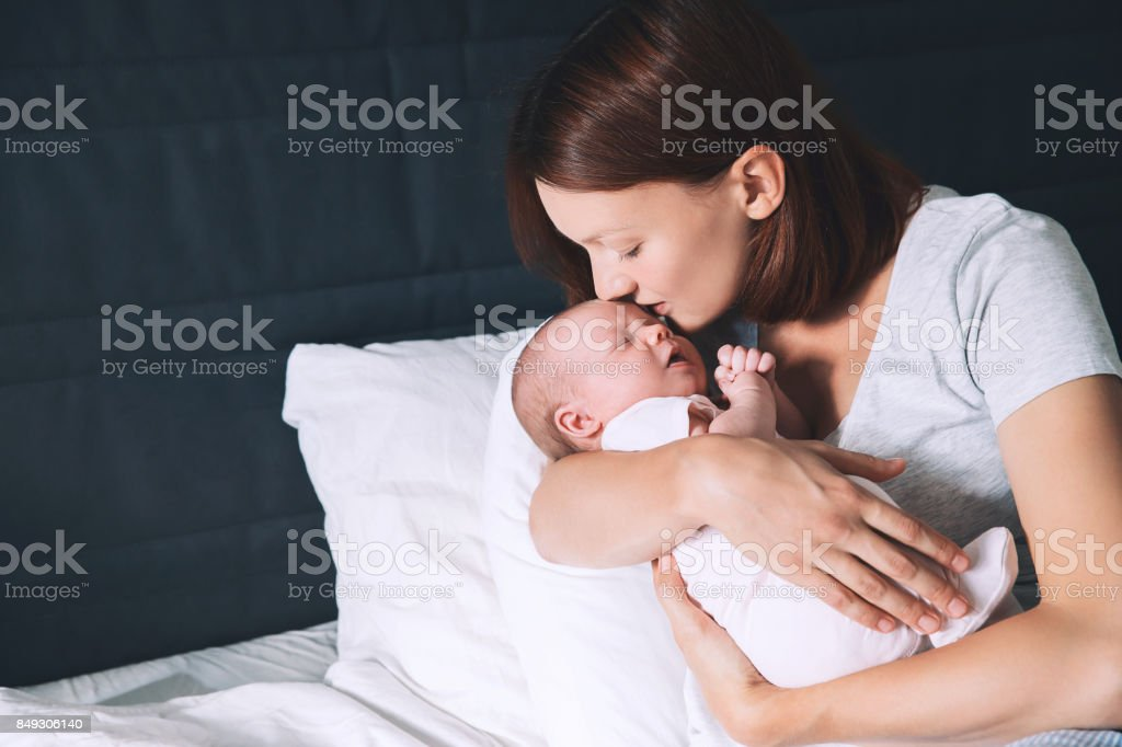 Newborn baby sleeping in the hands of his mother. stock photo