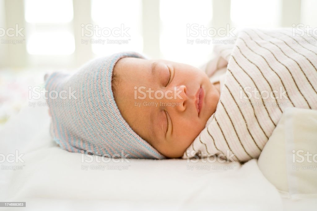 New-born baby sleeping on a bed wearing a blue hat stock photo