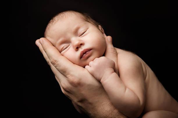 Newborn Baby Sleeping on Father Hand, New Born Kid Studio Portrait stock photo
