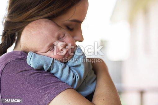istock Newborn baby sleeping on mother's shoulder 1068180364