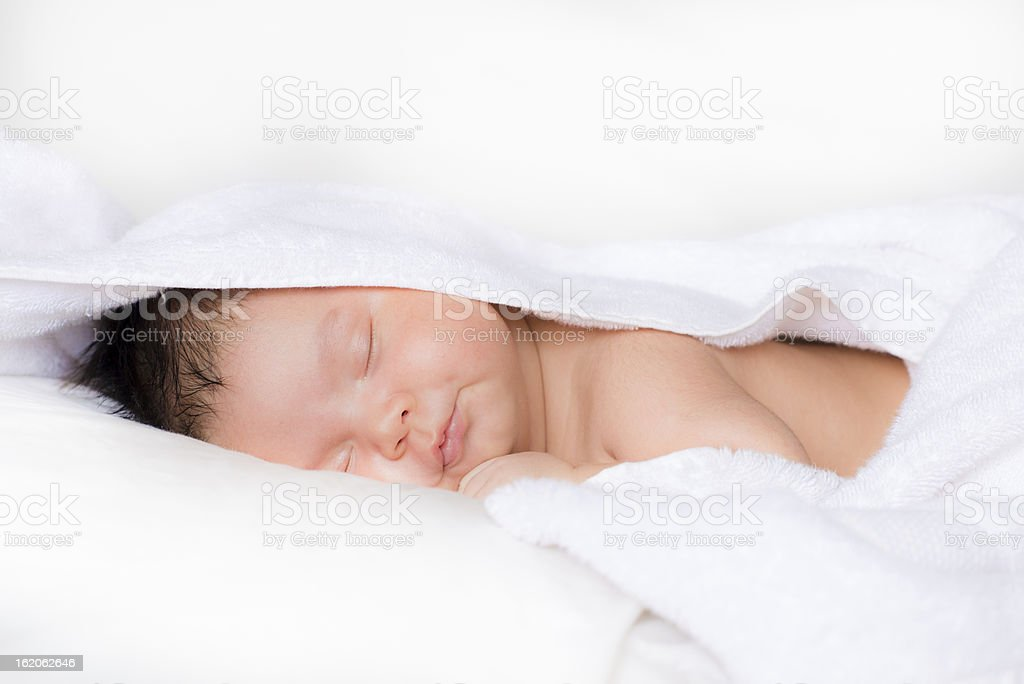 Newborn baby sleeping on white bed after his bath royalty-free stock photo