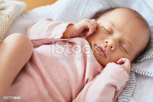 Newborn baby girl sleeping peacefully in the crib