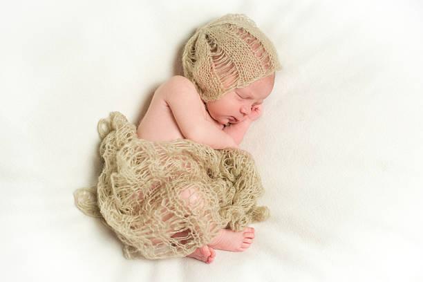 newborn baby sleeping with hand under his cheek - kindermütze häkeln stock-fotos und bilder