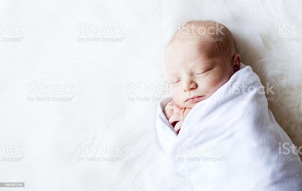 Newborn Baby Swaddled While on Fur Rug stock photo