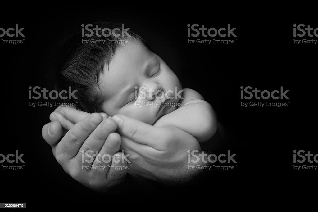 Newborn Baby taken closeup in father's Hand - black стоковое фото