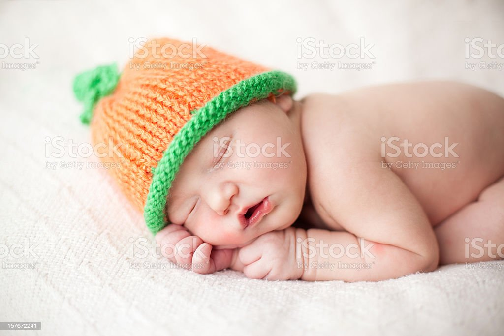 Newborn Baby Wearing a Pumpkin Style Hat royalty-free stock photo