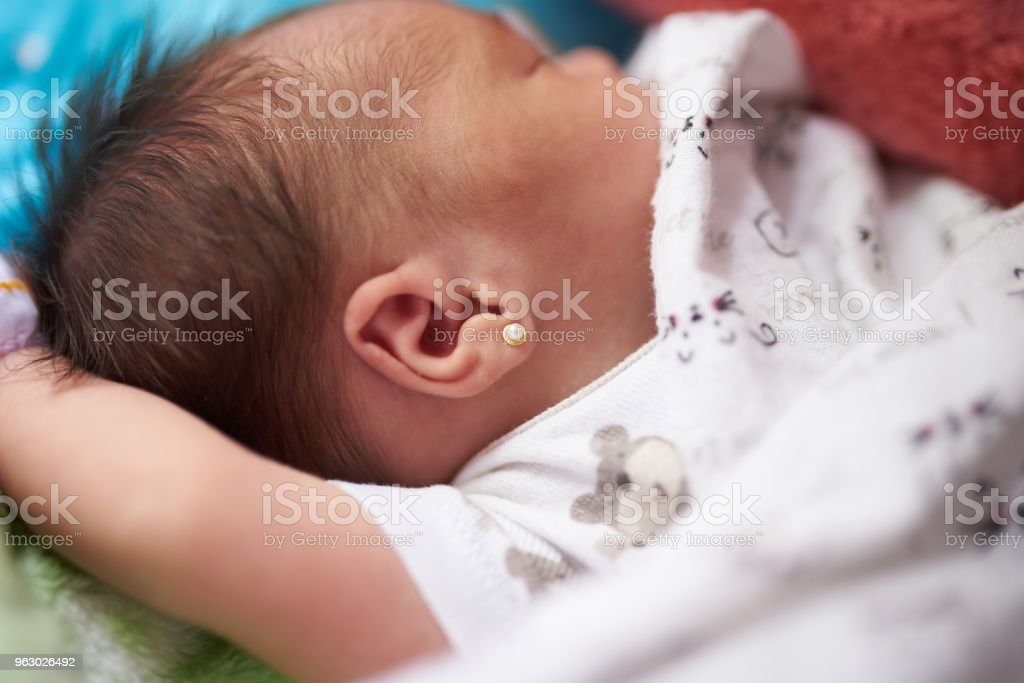 Newborn baby with earring stock photo