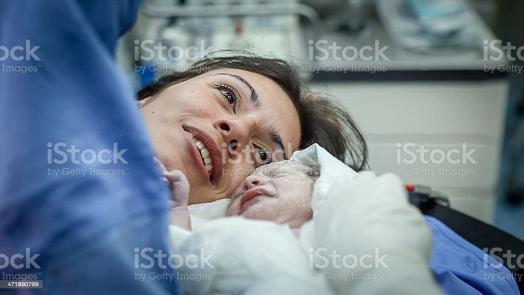 Newborn baby with her mother looking down stock photo