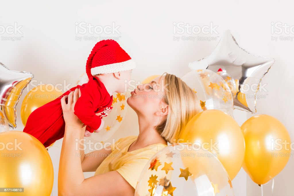 Newborn baby with mom on the background of Christmas balls stock photo