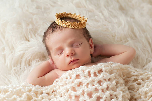 Newborn Baby with Prince's Crown Portrait of a 12 day old newborn baby boy wearing a gold crown. He is sleeping on a beige flokati rug with his hands behind his head. royalty stock pictures, royalty-free photos & images