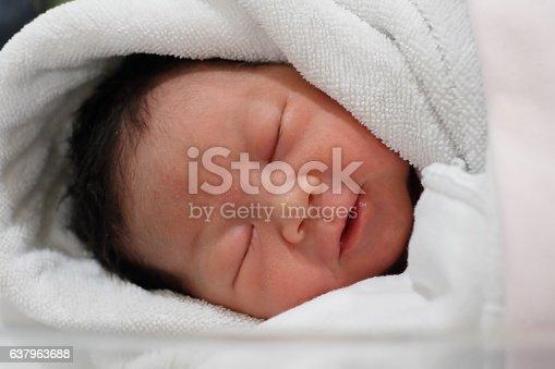 Newborn baby wrapped in white diaper