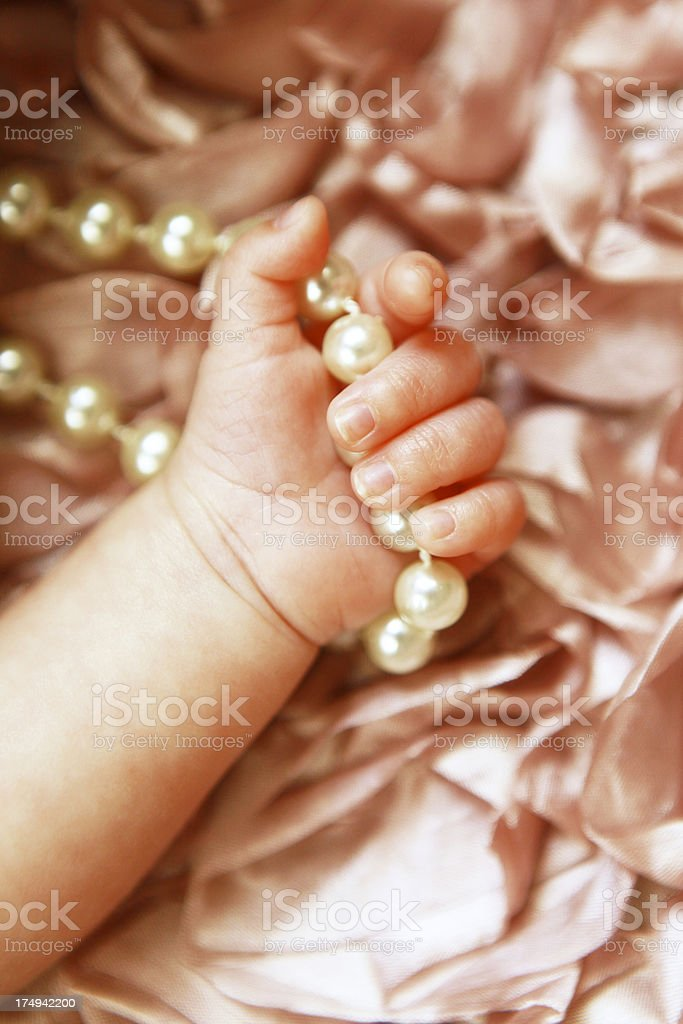 Newborn Baby's Hand Gripping Pearls royalty-free stock photo