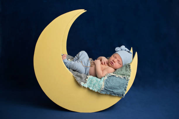 Newborn Boy Sleeping on the Moon stock photo