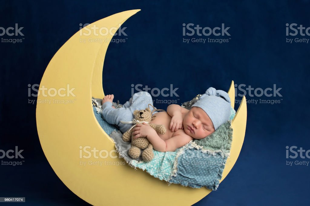 Newborn Boy Sleeping on the Moon with Teddy Bear stock photo