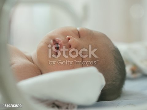 Asian newborn baby first days of life in nursery room at hospital.