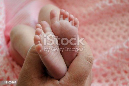Parent holds newborn feet over pink crochet blanket