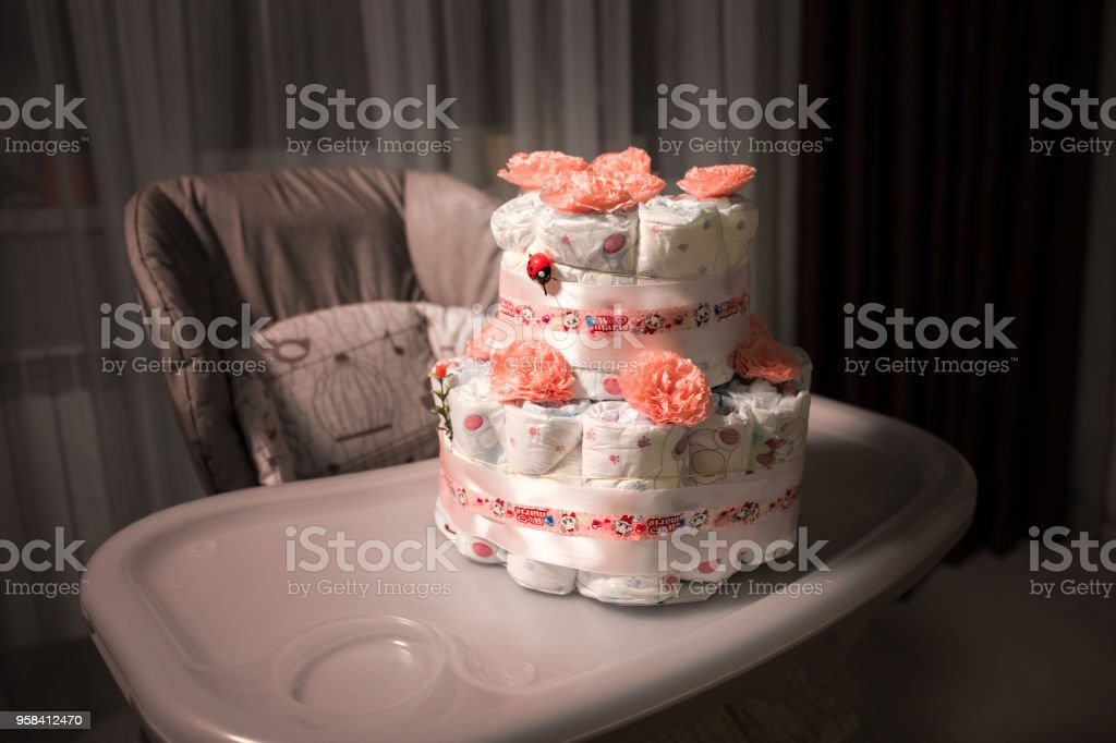 Newborn gift concept. Cake of diapers. Wrapped diapers as cake with flowers. Cake of wrapped clean diaper on table with baby doll decorated. stock photo