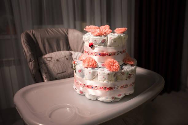 neugeborenen geschenk konzept. kuchen von windeln. verpackte windeln als kuchen mit blumen. kuchen des umschlossenen saubere windel auf tisch mit babypuppe dekoriert. - windel partys stock-fotos und bilder