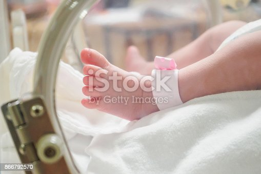 Newborn girl baby inside incubator in hospital post delivery room with identification bracelet tag name