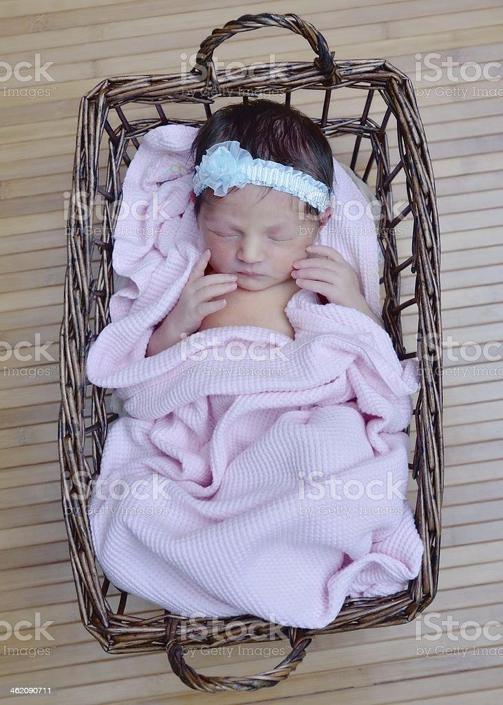 Newborn girl in a basket stock photo