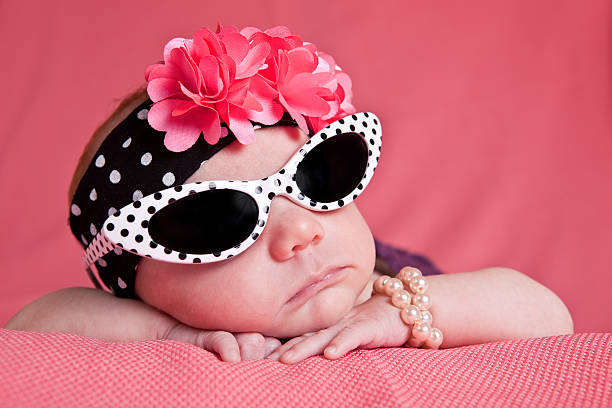 Newborn Girl in Sunglasses An adorable 1 month old baby girl dressed in sunglasses, headband and pearl bracelet. diva human role stock pictures, royalty-free photos & images