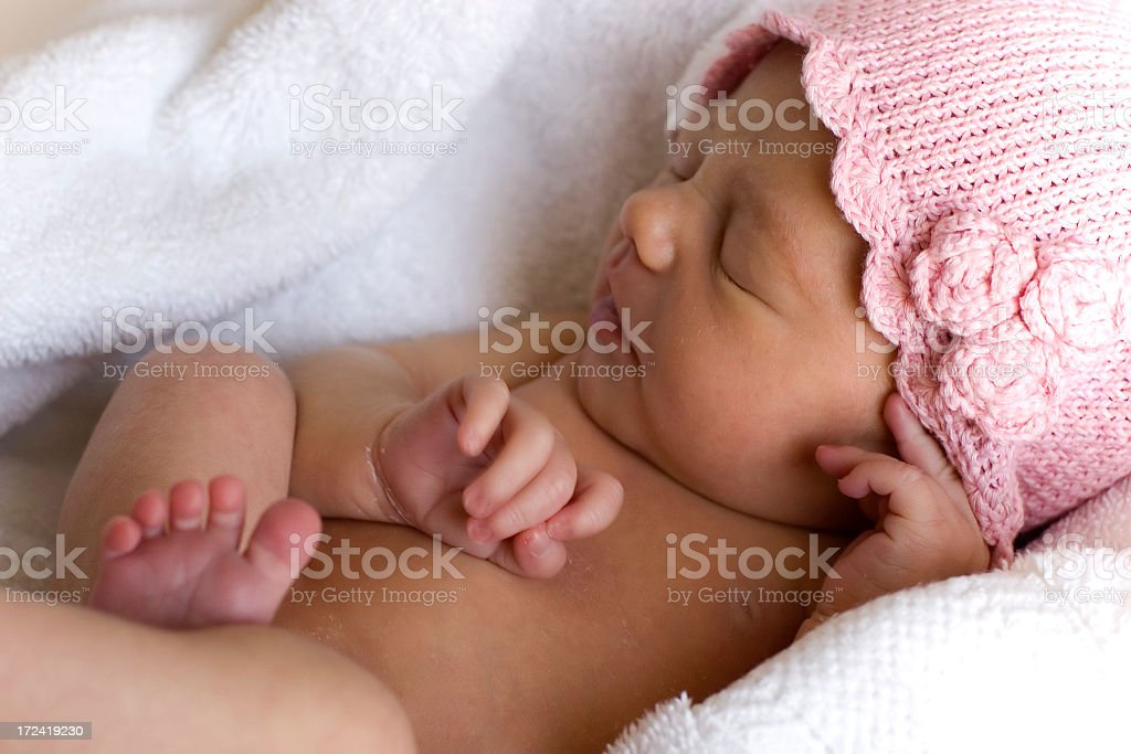 Newborn girl on towel in pink hat royalty-free stock photo