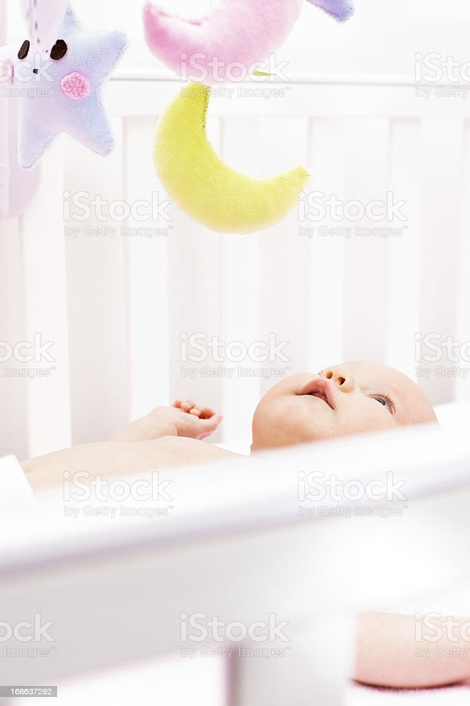 Newborn girl playing with toys in crib stock photo
