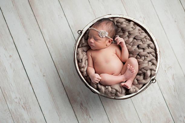 Newborn Girl Sleeping in Wooden Bowl stock photo