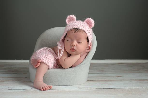 Newborn Girl Wearing a Pink Bear Hat stock photo