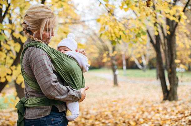 Newborn in baby sling carrier stock photo