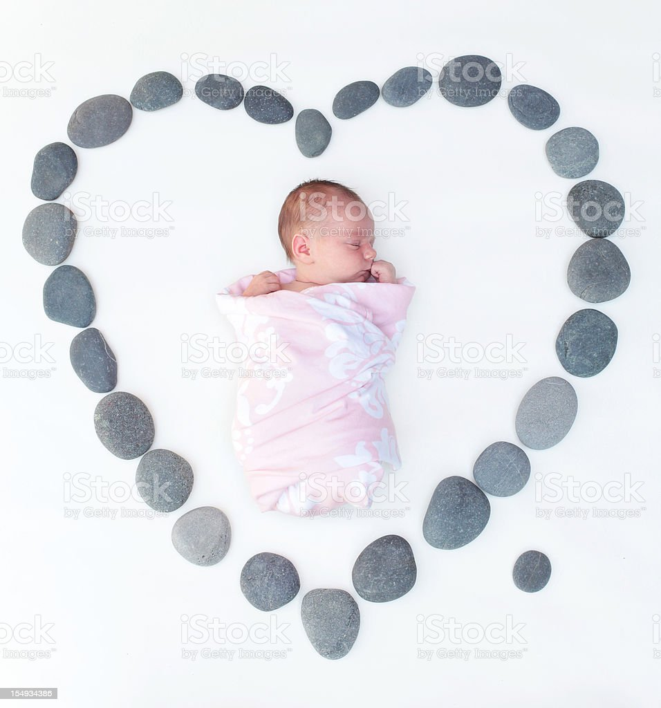 Newborn in Heart of Smooth River Stones stock photo