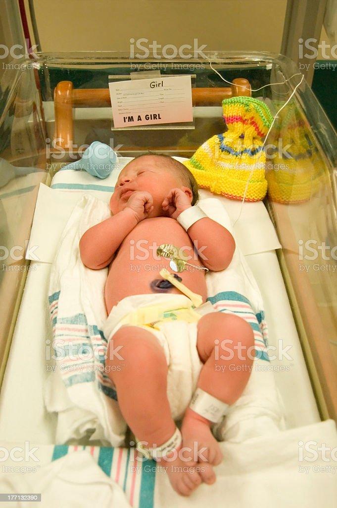 Newborn girl sleeping in warmer in nursery one day after birth.