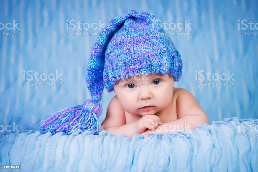 Newborn in knitted cap on a blue background. стоковое фото