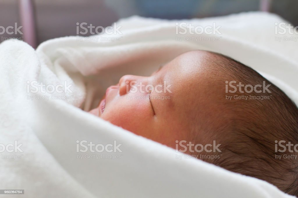 Newborn infant baby girl in white blanket sleeping in bed stock photo