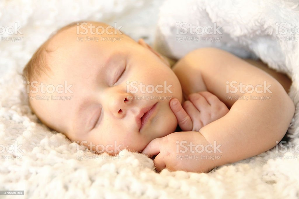 Newborn Infant Girl Sleeping Peacefully in White Blankets stock photo