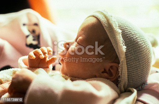 A horizontal image of a newborn baby profile. The young infant is sleeping and is wearing the stocking cap handed out in the delivery room. The infant's hand and thumb are near her mouth.