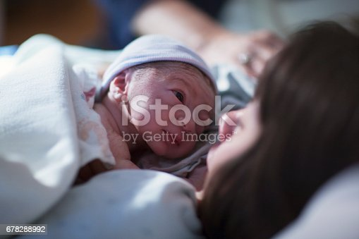 istock A newborn mixed race asian caucasian in a blue cap baby rest on his brunette asian mothers chest and stares into her eyes for the first time 678288992