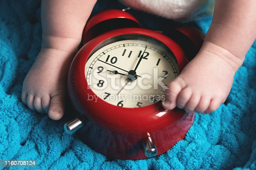 Baby feet and a red alarm clock on a blue towel background.