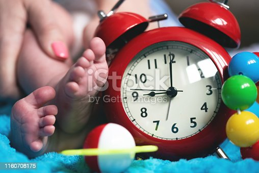 Baby feet, mother hands and red alarm clock with a toys.