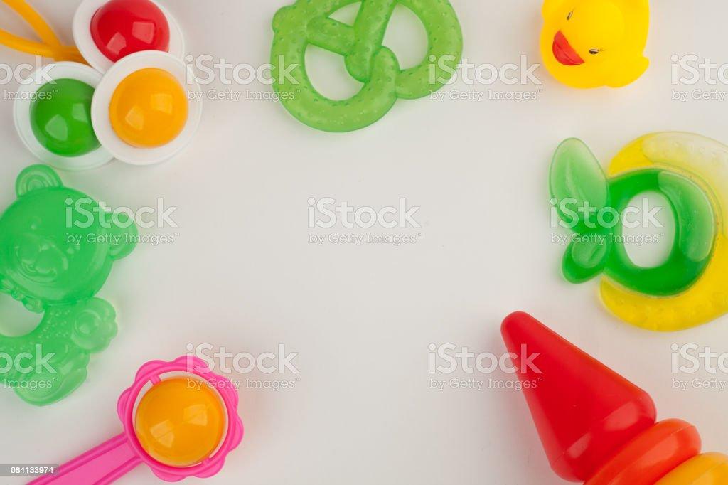 Nyfödd uppsättning leksaker av Bitring och färgglada skallror på vit bakgrund, ovanifrån, platt lay, kopia utrymme royaltyfri bildbanksbilder