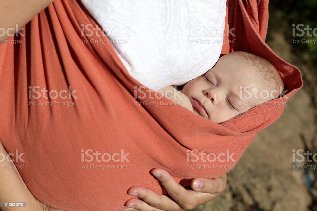 Newborn sleeping in baby sling carrier stock photo