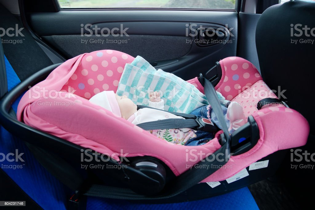 Newborn sleeping in car seat.Safety concept. Infant baby girl. secure driving with children. Cute baby sleeping in car. stock photo