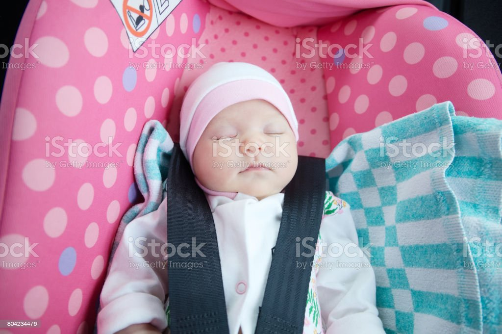 Newborn sleeping in car seat.Safety concept. Infant baby girl. secure driving with children. Baby care. Cute baby sleeping in car. stock photo