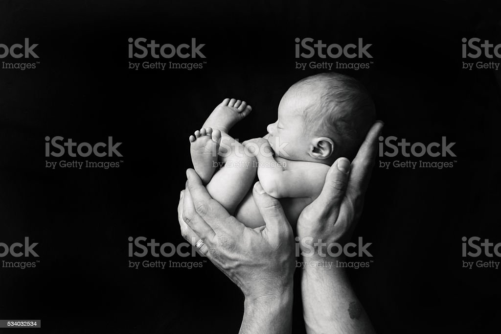 Black and white photo of father holding naked newborn baby pictures images and stock photos