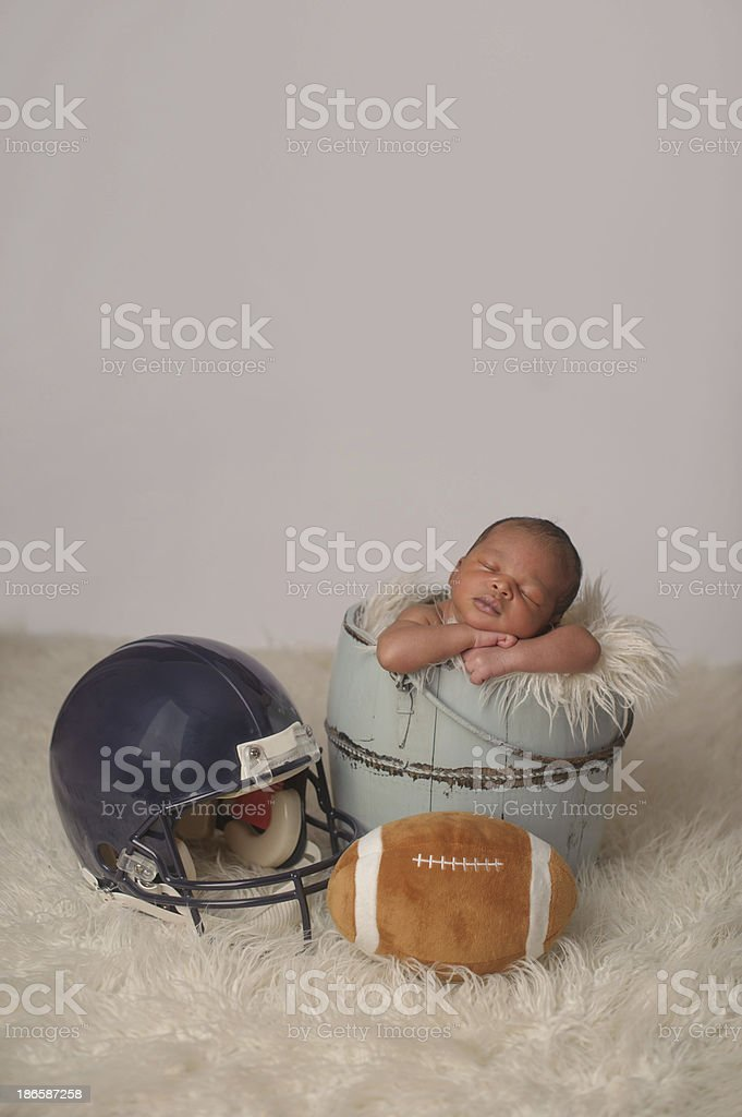 Newborn Sleeping with Football and Helmet stock photo