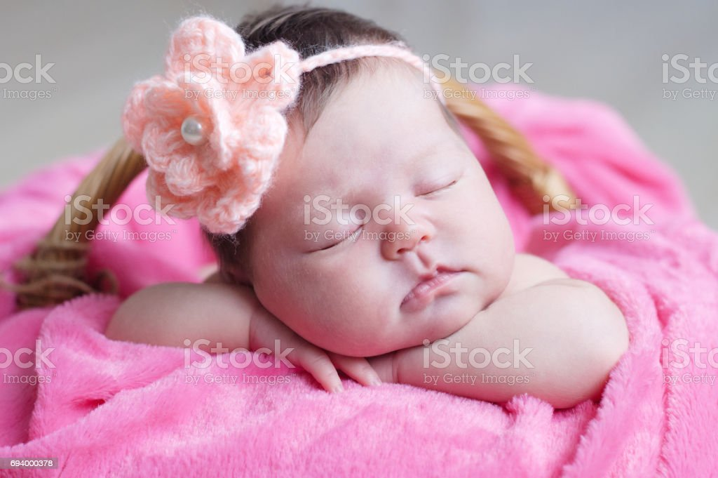 Newborn sleeping with knitted flower on head. Infant baby girl closeup lying on pink blanket in basket. Cute portrait of child stock photo