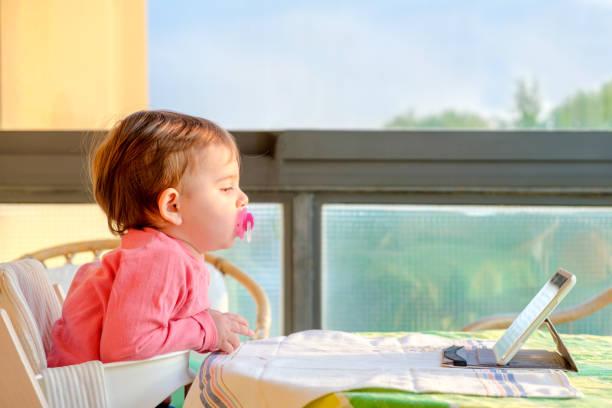 neugeborenen tablet tv digital native - kinderstuhl und tisch stock-fotos und bilder